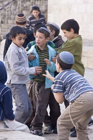 Children of traditional Jewish families are having a discussion while playing in the street of Jerusalem Old City.