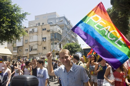 Blond young man with a rainbow Peace flag at Gay Pride Parade in Tel Aviv, Israel, on 6102011  Gay Pride Parades were held in numerous countries during month of June with people of sexual minorities voting for their rights.  http:en.wikipedia.orgwi Editorial