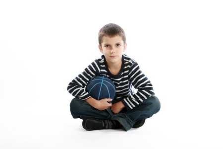 Studio shot of a boy holding the basketball ball while sitting on the floor (isolated on white) photo