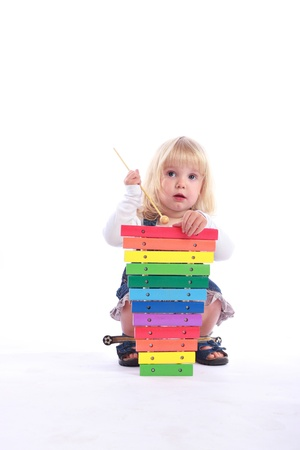 Studio shot of a cut little girl playing a colorful musical toy.