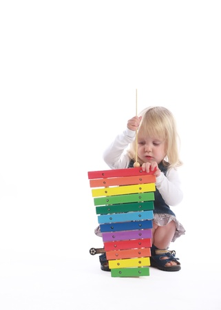 Studio shot of a small blonde girl playing a musician with her first sound-providing toy.