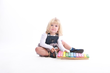 Studio shot of a cute little blonde girl playing a rainbow-colored musical toy. photo