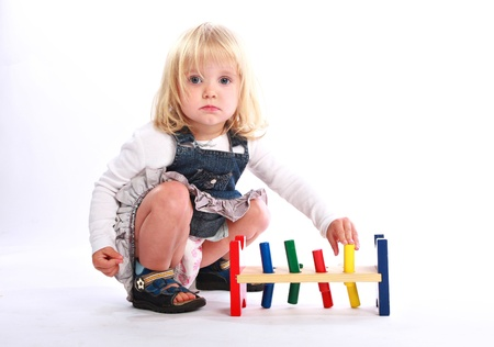Studio shot of a sweet little blonde model playing a colorful toy for learning colors and cause-and-effect principle. photo