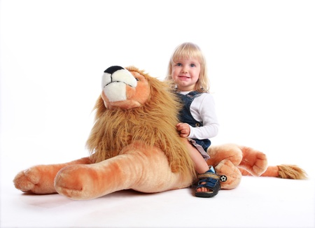 Studio shot of a blonde little girl riding happily her toy lion. photo