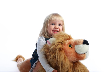 Studio shot of a happy blonde little girl riding her toy lion photo