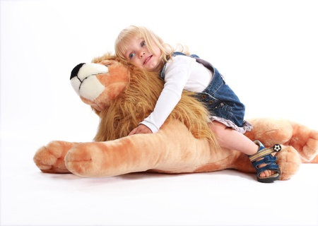 Distressed blonde little girl leaning on her favourite toy lion for consolence.
