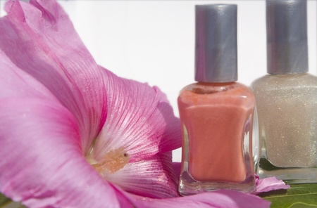 Two bottles on nail polish with a pink flower and a leaf.