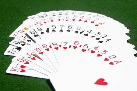 Mazo completo de cartas colocadas en la mesa de juego verde según los palos.