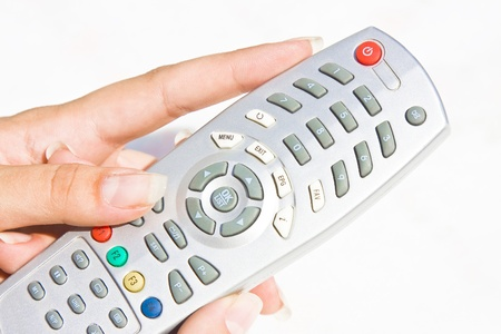 Beautiful hand of a woman holding a TV control.