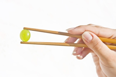 Beautiful hand of a woman holding a green grape with chinese sticks against white background.
