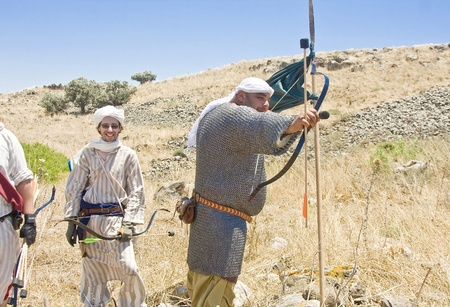 sword act: Men clad as Saracene archers during event of historical reenactment on the historical location of the Battle of Hattin in Israel. Historical reenactment is a popular hobby for history lovers worldwide. The Battle of Hattin (Qarne Hittim) was a crucial fig Editorial