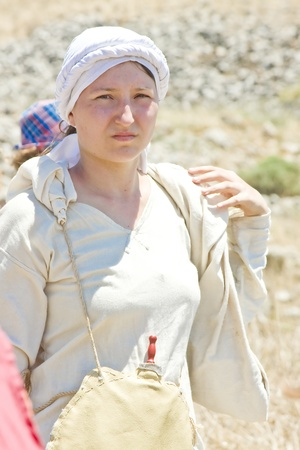 reenact: Young woman clad in medieval clothes during the event of historical reenactment on the historical location of the Battle of Hattin in Israel. Historical reenactment is a popular hobby for history lovers worldwide. The Battle of Hattin (Qarne Hittim) was a