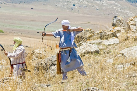 sword act: A man clad as a Saracene aiming for the crusaders with his bow during the historical reenactment of the Battle of Hattin in Israel. Historical reenactment is a popular hobby for history lovers worldwide. The Battle of Hattin (Qarne Hittim) was a crucial f