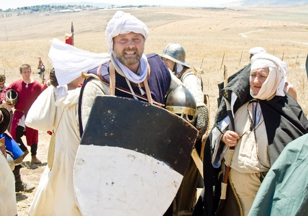 sword act: People acting Crusaders and army followers after the event of historical reenactment on the historical location of the Battle of Hattin in Israel. Historical reenactment is a popular hobby for history lovers worldwide. The Battle of Hattin (Qarne Hittim)