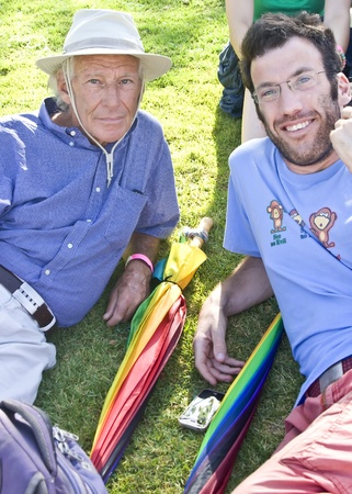 Jerusalem, Israel - July 28, 2011 - Male couple with rainbow umbrellas resting on the greens before the Gay Pride March in Jerusalem, Israel.