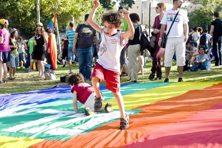 Jerusalem, Israel - July 28, 2011 - Little boy playing on the huge rainbow flag during the preparations for the Pride Parade in Jerusalem, Israel. Stock Photo - 10274105