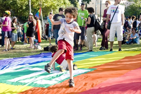 Jerusalem, Israel - July 28, 2011 - Little boy dancing on the great rainbow flag during the preparation to the Pride Parade in Jerualem, Israel (motion blur). Stock Photo - 10274103