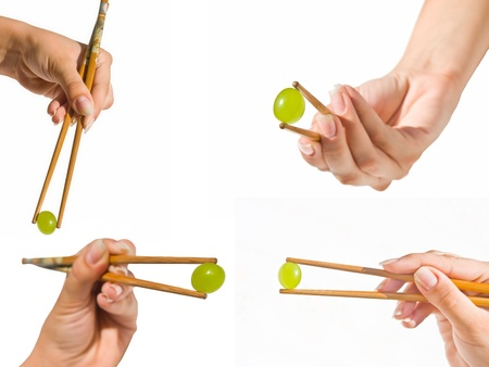 Set of womans hands holding a grape with Chinese sticks at various angles. Stock Photo