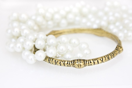 Set of brass bracelet and a lace of imitation perals on white. Stock Photo