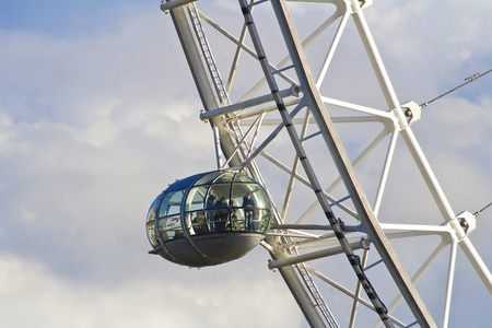 Close up on the London Eye capsule in London skies with clouds.