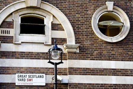 Brick wall on the Scotland Yard street with a street lamp.