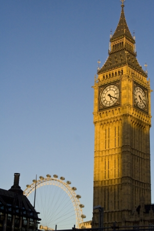 Famous clock tower of Big Ben and London Eye in London against sunset lighting.