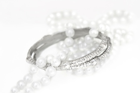 A set of accessories consisting of two silver bracelets and imitation pearls on white.