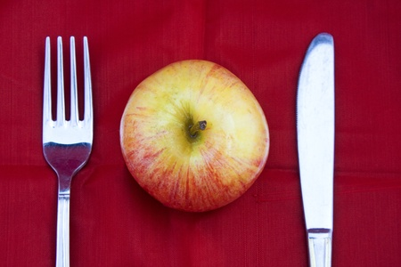 Golden-red juicy apple ready for healthy breakfast with fork and knife on red background. Stock Photo