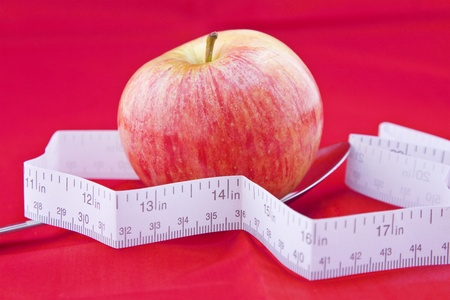 A red apple in a spoon with a paper meter around it standing for the organic food, dieting, and healthy lifestyle.