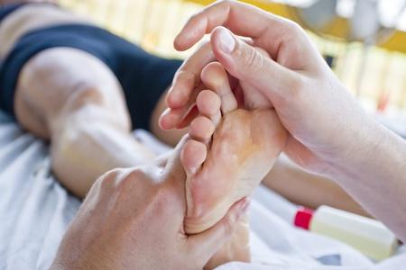 massage pied: Gros plan sur les mains de massoth�rapeute, tout en traitant un coureur