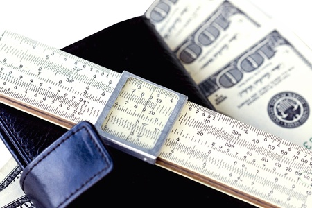 A black leather moleskin, a logarithmic scale ruler, and several hundred dollar bills on white background