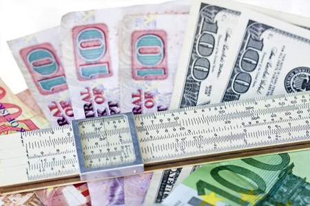 width: Scale ruler placed across money bills of different countries.