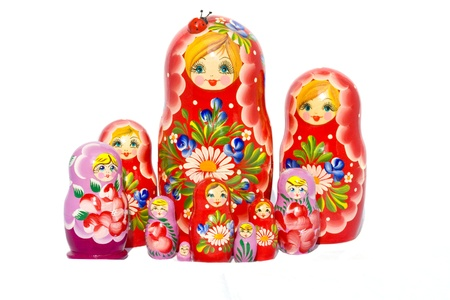 Red and violet Matryoshka doll families against white background.