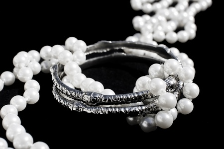 A line of imitation pearls twining two silver bracelets over black background.