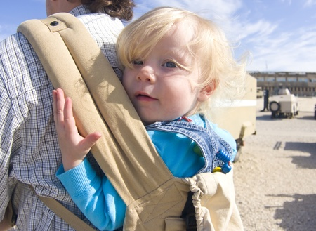 A cute blonde toddler girl in a baby carrier on her fathers back.