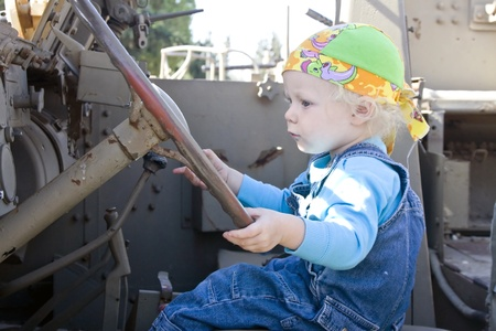 Cute blonde baby girl at a driving wheel of an old armor vehicle. photo