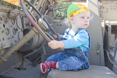 Baby girl looking back while playing with armor vehicle driving wheel