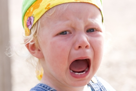Close-up of a blond baby girl bawling furiously (focus on the left eye and the mouth).