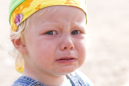 Close-up picture of a cute baby girl in angry tears. Stockfoto