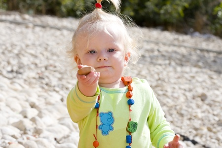 upsweep: Cute baby girl holding out a pebble to play. Stock Photo