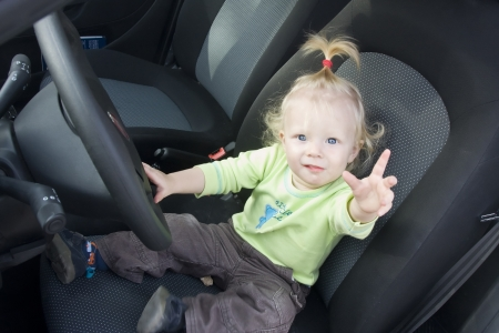Cute toddler girl waves her hand from the driving wheel.