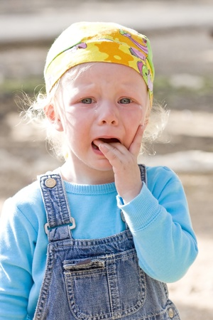 Cute blonde little girl is crying being scared  photo