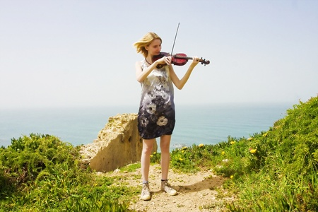 Young pretty blonde girl playing violin in a meadow near the sea. photo
