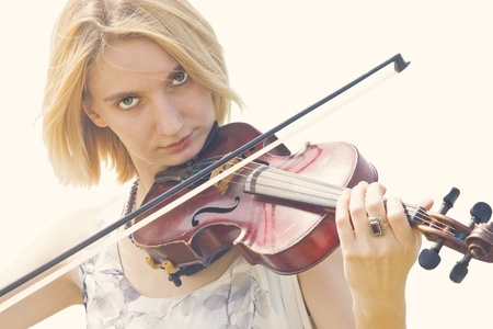 Beautiful blonde girl playing old violin (isolated on white) photo