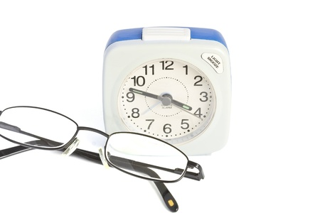 beeping: Alarm clock and folded glasses over white background  Stock Photo