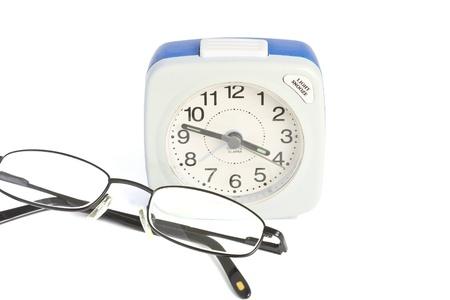 Alarm clock and folded glasses over white background Stock Photo - 13146842