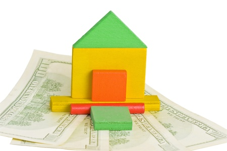 Wood model of a house standing on the dollar bills - isolated over white  photo