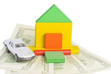 Wood model of a house and a toy car standing on the hundred-dollar bills - isolated over white  photo
