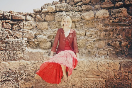 Beautiful young girl in red clothes sitting on the old stone wall  photo