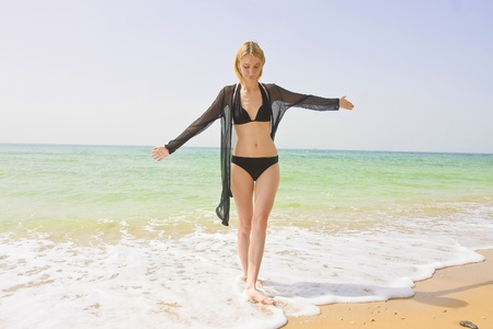 bathing   suit: Beautiful young girl balancing in the wave on a beach